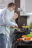 Happy couple preparing food in kitchen Stock Photo