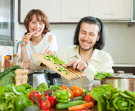 Happy couple preparing a meal of vegetables Stock Photography