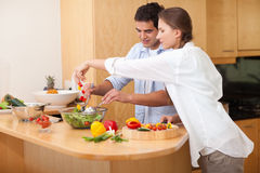 Happy couple preparing a salad Royalty Free Stock Photos