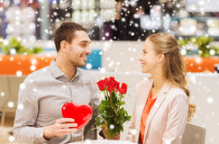 Happy couple with present and flowers in mall. Love, romance, valentines day, couple and people concept - happy young men with red flowers giving present to Royalty Free Stock Photography