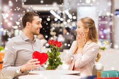 Happy couple with present and flowers in mall. Love, romance, valentines day, couple and people concept - happy young men with red flowers giving present to Stock Photo