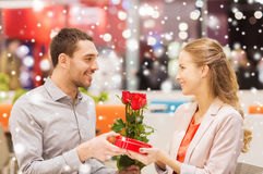 Happy couple with present and flowers in mall. Love, romance, valentines day, couple and people concept - happy young men with red flowers giving present to Stock Photos