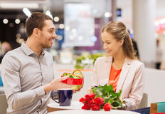 Happy couple with present and flowers in mall Stock Photography