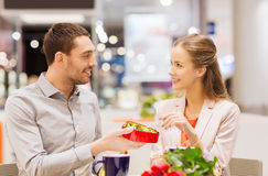 Happy couple with present and flowers in mall Stock Images