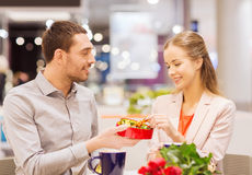 Happy couple with present and flowers in mall Royalty Free Stock Images