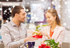 Happy couple with present and flowers in mall. Love, romance, valentines day, couple and people concept - happy young couple with red flowers and open gift box Royalty Free Stock Images