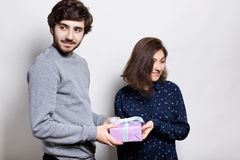A happy couple with present. A hipster guy presenting a gift to his girlfriend looking aside. Young male and female isolated over. White background. People and stock photos