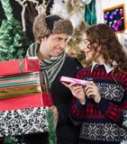 Happy Couple With Presents In Christmas Store Royalty Free Stock Images