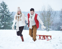 Happy couple pulling sled in winter Stock Photo