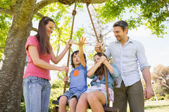 Happy couple pushing kids on swing Royalty Free Stock Photo