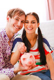 Happy couple putting coin in piggy bank Stock Photo