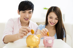 Happy couple putting coin into piggy bank. Young happy couple putting coin into piggy bank royalty free stock photo