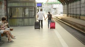 Happy couple on railway station, young family walking on rail platform, holding hands. Romantic trip stock footage