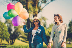 Happy couple with rainbow-colored air balloons in a park. Happy girls with rainbow-colored air balloons in a park Royalty Free Stock Image