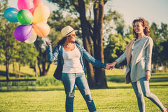 Happy couple with rainbow-colored air balloons in a park. Happy girls with rainbow-colored air balloons in a park Stock Photo