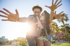 Happy couple raising hands in sunlight having fun. Portrait of happy couple raising hands in sunlight having fun Royalty Free Stock Image