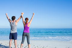 Happy couple raising their hands Royalty Free Stock Photo