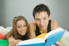 Happy couple reading a book Stock Photography