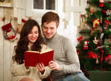 Happy couple reading book on background Christmas decorations Stock Photography