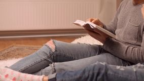 Happy couple reading book at home. Leisure, hygge and people concept - happy couple reading book at home stock video