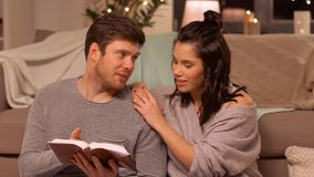 Happy couple reading book at home. Leisure, hygge and people concept - happy couple reading book at home stock video footage