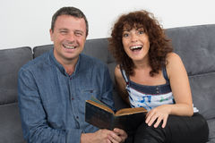 Happy couple reading book and laughing having fun Stock Photo