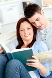 Happy couple reading a book in the living-room Stock Images