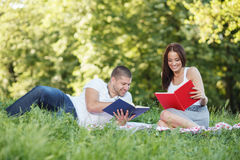 Happy couple reading book in park Royalty Free Stock Photos