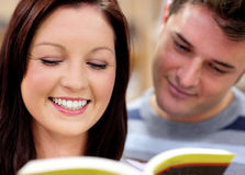 Happy couple reading a book together Stock Photography