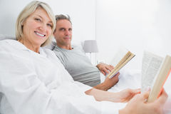 Happy couple reading books in bed Royalty Free Stock Image