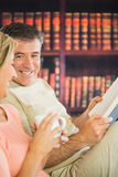 Happy couple reading books and drinking coffee in a reading room Stock Image
