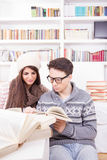 Happy couple reading books at home royalty free stock photography