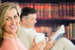 Happy couple reading and drinking coffee in a reading room Royalty Free Stock Photography