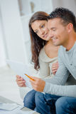 Happy couple reading letter on couch at home Stock Image