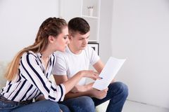Happy couple reading mail and checking accountancy looking each other sitting on a couch at. Home stock image