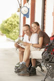 Happy Couple Reading Map On Bench Royalty Free Stock Photography