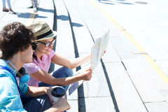 Happy couple reading map while sitting on steps outdoors Stock Images