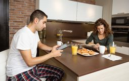 Happy couple reading news in a home breakfast Stock Photography