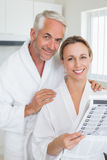 Happy couple reading newspaper together in bathrobes Royalty Free Stock Photos