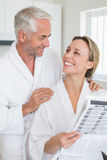 Happy couple reading newspaper together in bathrobes Stock Image