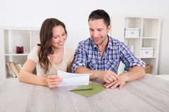 Happy couple reading paper. Portrait Of A Happy Young Couple At Home Reading Paper Stock Photos