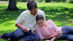 Happy couple reading while sitting on the grass stock video