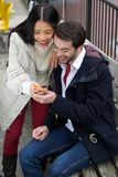 Happy couple reading text message on mobile phone Royalty Free Stock Photo