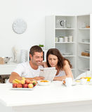 Happy Couple Reading The Newspaper In The Kitchen Stock Photo
