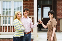 Happy couple with real estate agent. Happy couple getting keys to new house from real estate agent Royalty Free Stock Photography