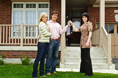 Happy couple with real estate agent. Happy couple getting keys to new house from real estate agent Royalty Free Stock Image