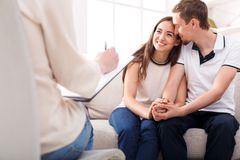 Happy couple reconciling at therapy session. In psychotherapists office Stock Photos