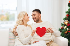 Happy couple with red heart at home for christmas Stock Image