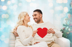 Happy couple with red heart at home for christmas Stock Photography