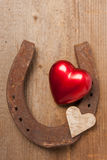 Happy couple. Red heart and a horseshoe on a wooden board Royalty Free Stock Photography